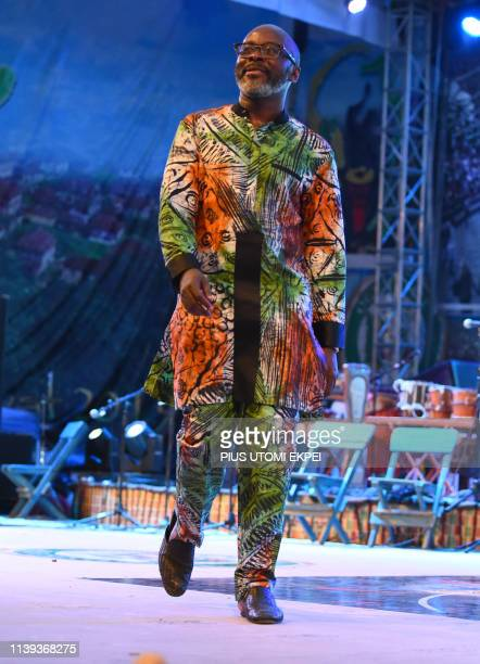 A man displays fashion designed with local Adire tie and dye fabrics during the opening of the fourth edition of African drum festival at the...