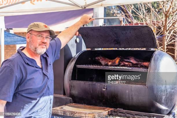 l'homme affiche sa viande sur le gril de barbecue au marché d'irene - four people photos et images de collection