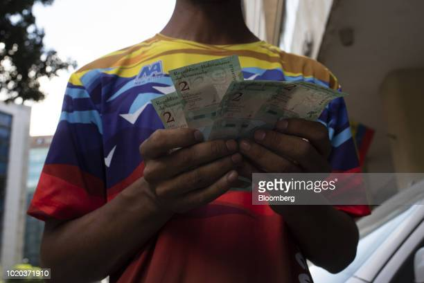 Man displays new 2 sovereign bolivar banknotes for a photograph after withdrawing them from an automated teller machine in Caracas, Venezuela, on...