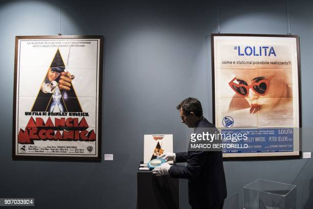 A man displays objects from the collection Cinema Stanley Kubrick near posters for the films Lolita and A Clockwork Orange at the Aste Bolaffi...