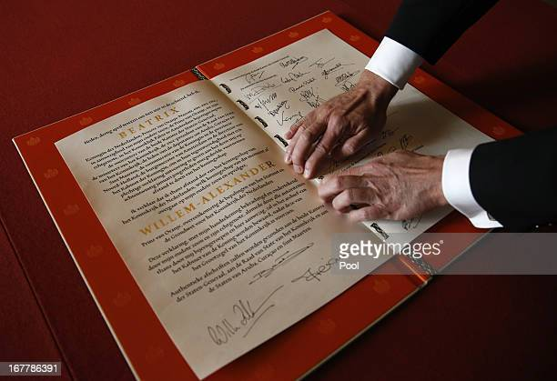 A man displays the Act of Abdication signed by Queen Beatrix of the Netherlands her son Prince WillemAlexander of the Netherlands and his wife...