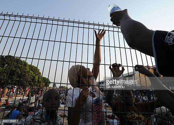 A man distributes a bottle of water to people waiting behind a fence in a refugee camp near the airport in Bangui after fleeing violence on December...