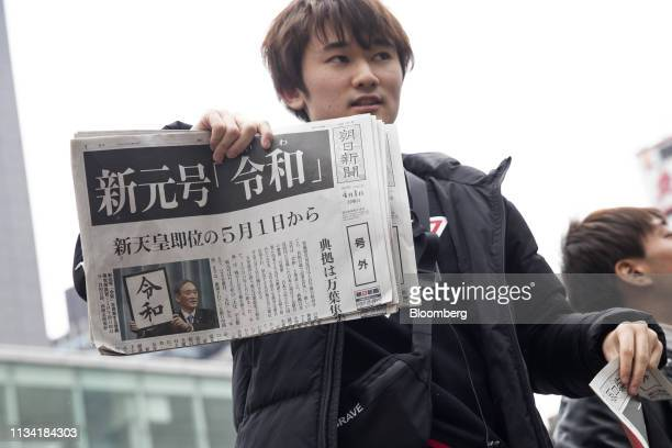 A man distributes copies of an extra edition of the Asahi Shimbun newspaper reporting on the announcement of the name of Japan's next imperial era...