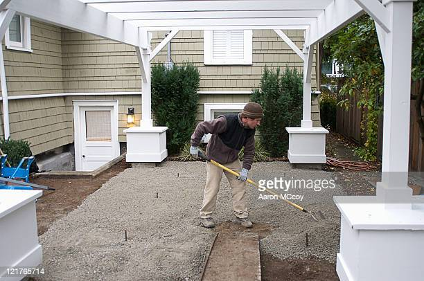 man distributes gravel for patio, seattle, washington - gravel stock pictures, royalty-free photos & images