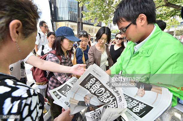 A man distributes special extra editions of a newspaper to passersby in Tokyo on August 8 reporting on a speech by Japanese Emperor Akihito to the...