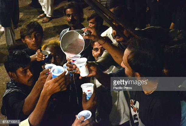 Man distributing the drink among the visitors of Juloos on the 7th day of Mhurram Ul Harram from fakir ka pir, Pakistan.