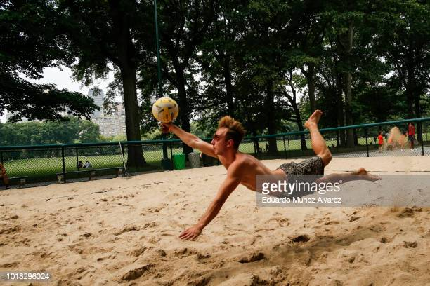A man dives for the ball playing beach volleyball during a warm day at Central Park on August 17 2018 in New York City Severe thunderstorms and even...