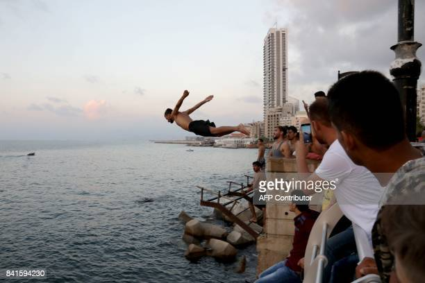 A man dives from Beirut's corniche in the Lebanese capital on September 1 during Eid alAdha holiday Muslims across the world celebrate the annual...