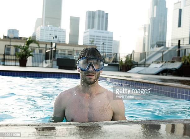 man dives in his swimming pool with diving mask