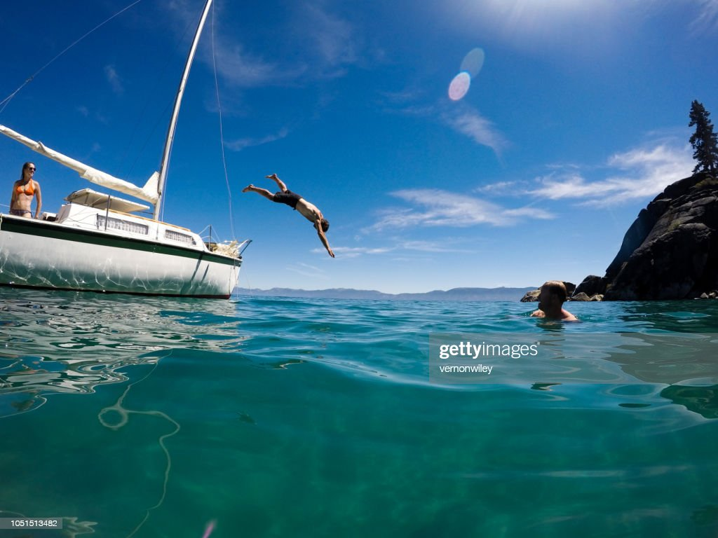Man dives into beautiful green waters off sailboat : Stock Photo