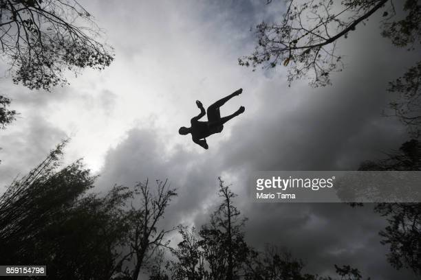 A man dives into the Espiritu Santo river from a rope swing before heavy afternoon rains more than two weeks after Hurricane Maria hit the island on...
