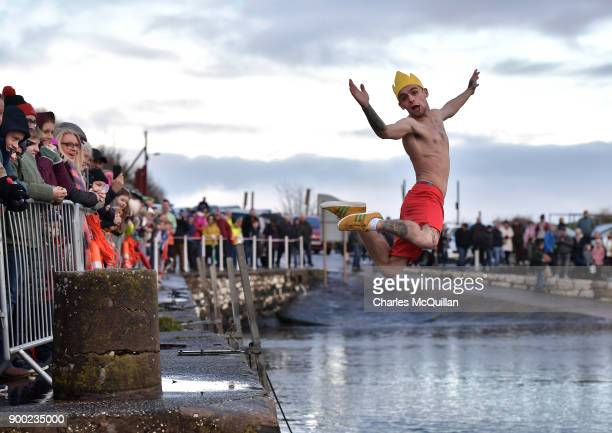 A man dives into the icy waters as swimmers take part in the annual New Years Day swim at Carnlough harbour on January 1 2018 in Carnlough Northern...