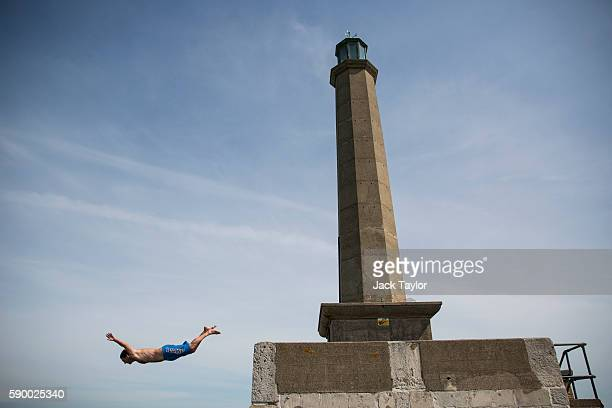 Man dives into the North Sea from beneath a lighthouse on the Margate Harbour Arm on August 16, 2016 in Margate, England. British holidaymakers and...
