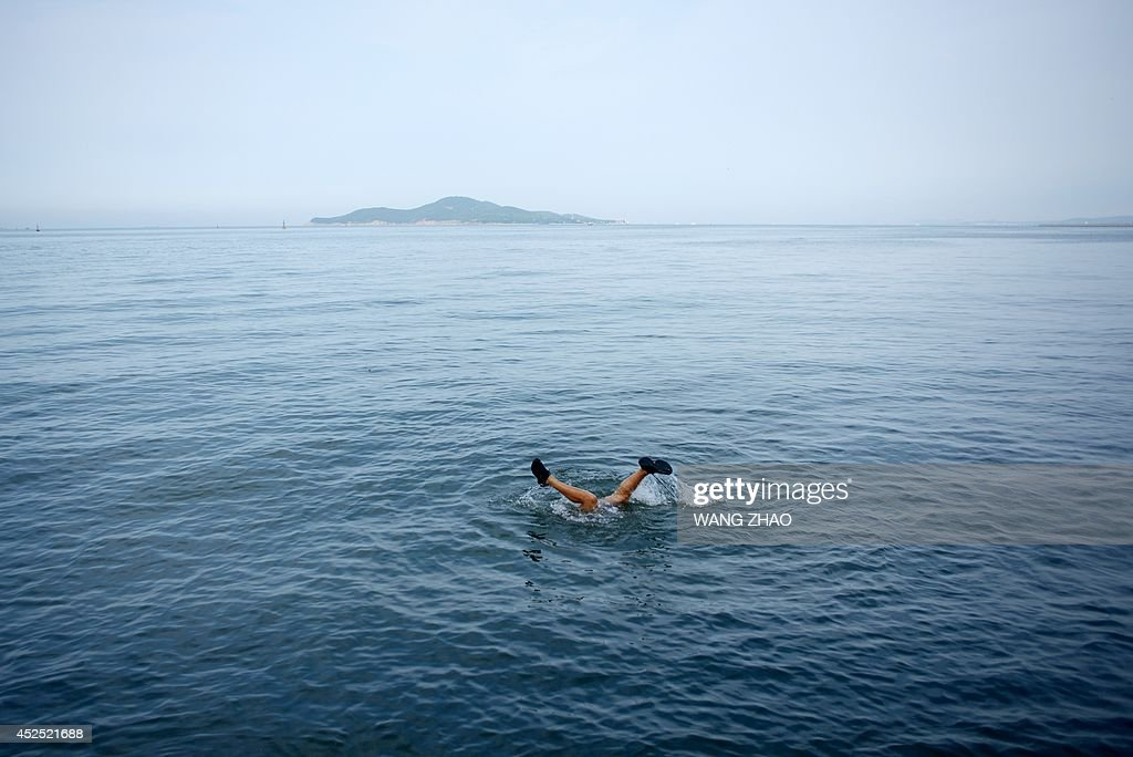 A man dives into the sea to catch fish in Weihai, east China's Shandong province on July 22, 2014. Tens of thousands of domestic tourists visit the coastal city during summer.