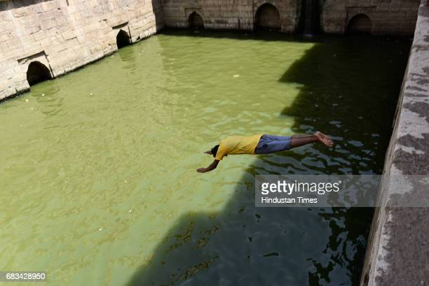 A man dives into the water of stepwell at Nizamuddin Dargah on a hot summer day on May 15 2017 in New Delhi India Heat wave conditions prevailed in...