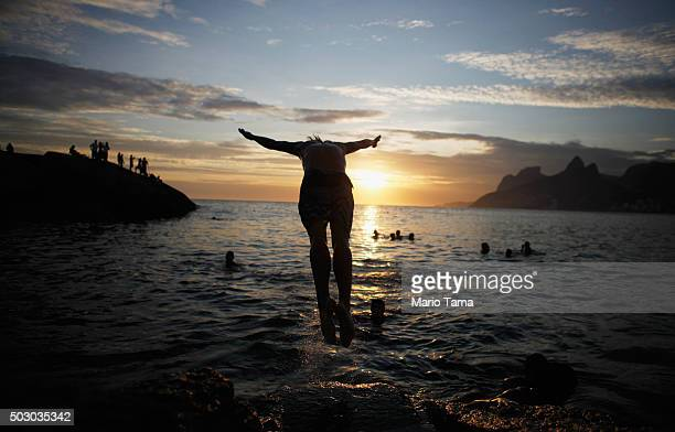 A man dives off Arpoador rock as people gather to watch the last sunset of 2015 on New Year's Eve on December 31 2015 in Rio de Janeiro Brazil More...
