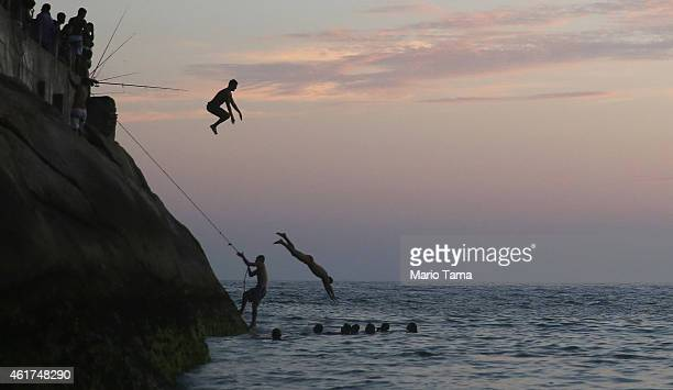 A man dives off the rocks at Leme Beach on January 18 2015 in Rio de Janeiro Brazil US government scientists reported that 2014 was the hottest year...