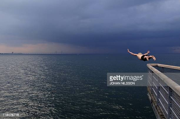 Man dives on July 3, 2011 from a bridge offering a panoramic view in Malmoe with thunderclouds gathering over Denmark on the other side of the...