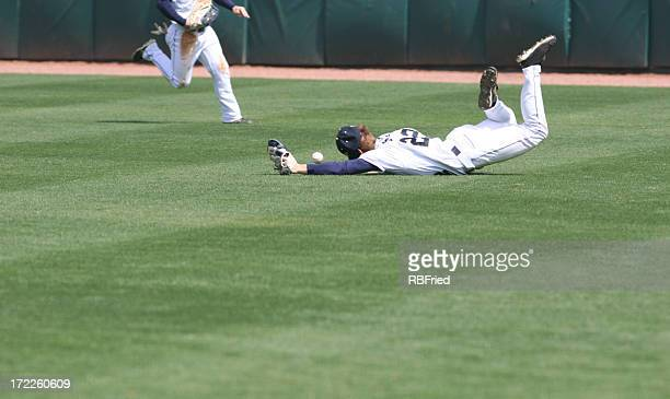 Man diving and missing the catch in baseball