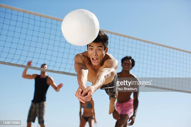 man diving for volleyball on beach - volleyball stock pictures, royalty-free photos & images