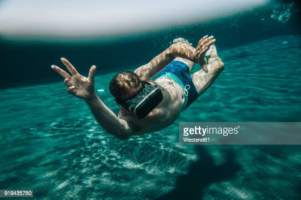 Man diving in a swimming pool wearing VR glasses