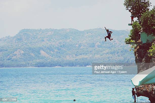 Man Diving In Sea Against Mountain