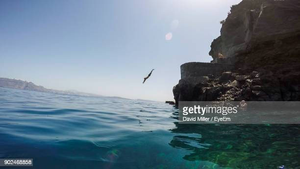 man diving in sea from cliff - david cliff stock pictures, royalty-free photos & images