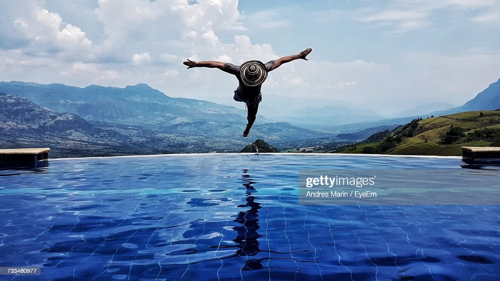 Man Diving In Swimming Pool By Mountains Against Sky : Stock Photo