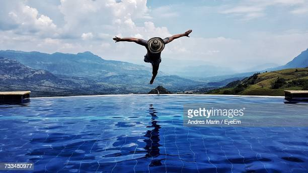 man diving in swimming pool by mountains against sky - diving into water stock photos and pictures