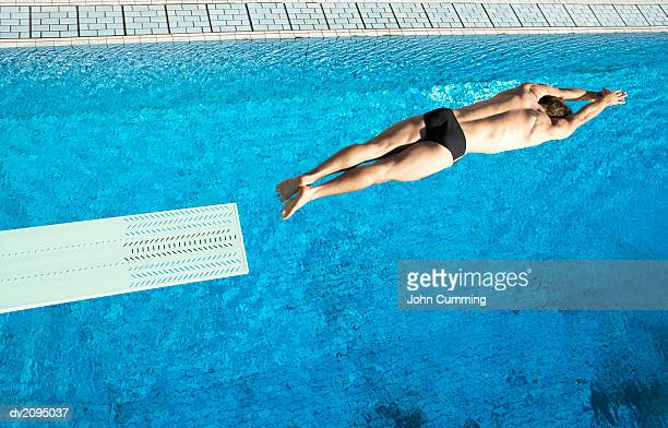 Man Diving Into a Swimming Pool From a Board