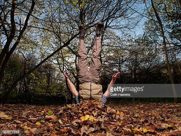 man diving into Autumn leaves