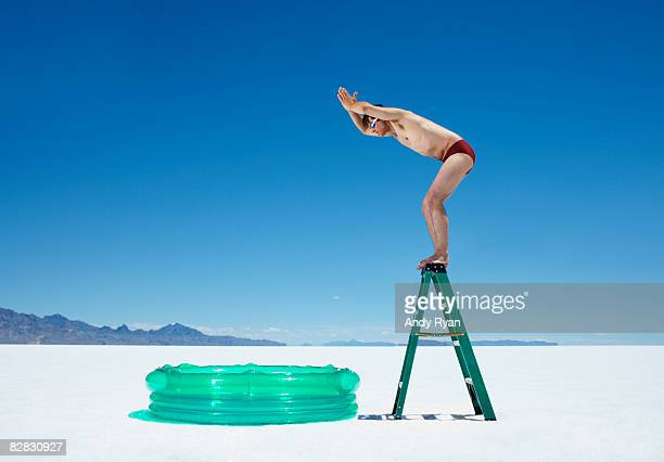 man diving into inflatable pool from ladder. - careless stock pictures, royalty-free photos & images