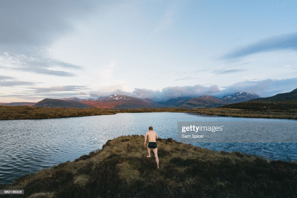 Man diving into lake during sunset : Stock Photo