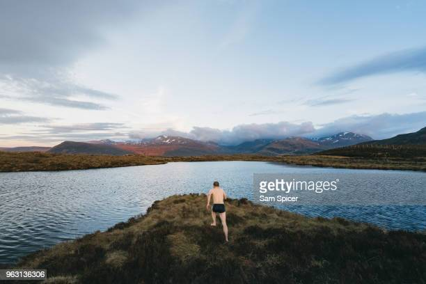 man diving into lake during sunset - diving into water stock photos and pictures