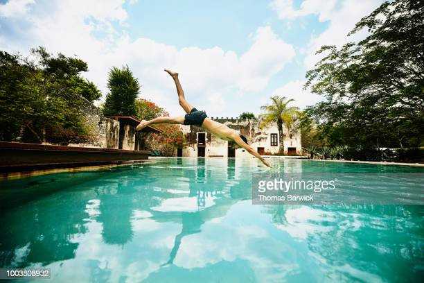 Man diving into pool at luxury tropical resort