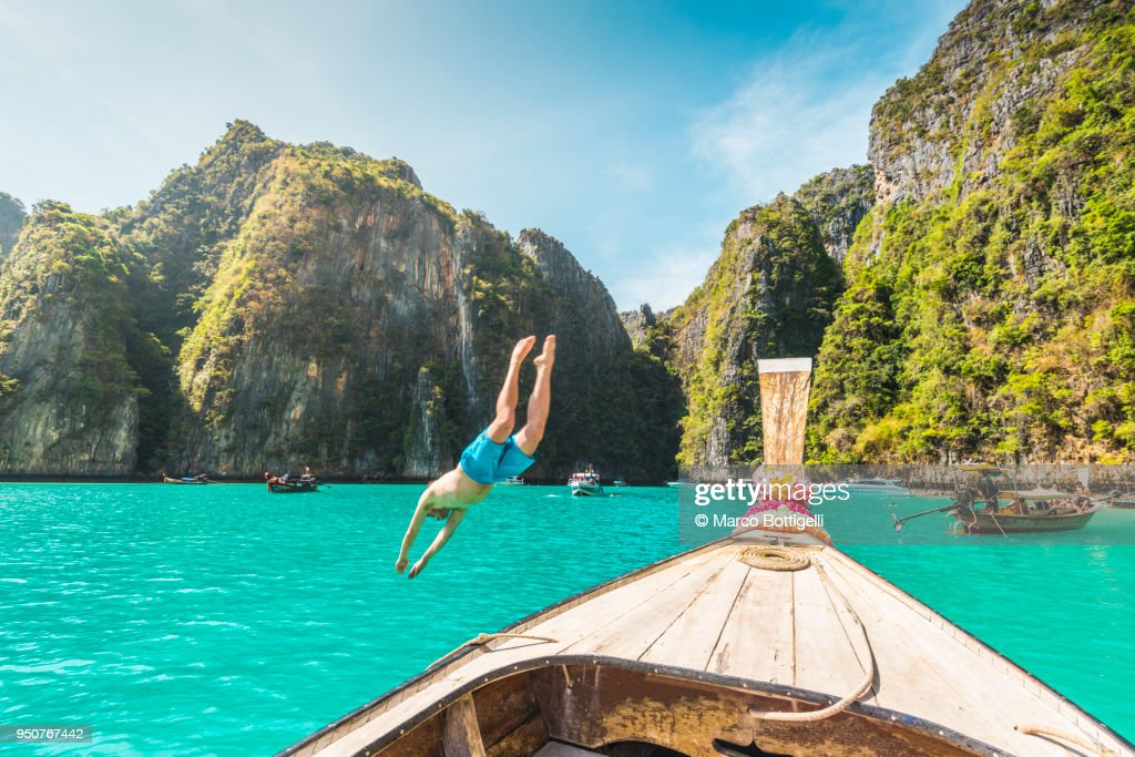 Man diving into water from a longtail boat. Phi Phi Islands, Thailand. : Foto de stock
