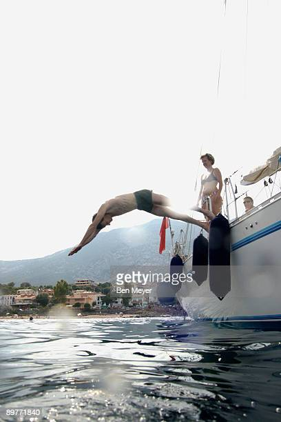 man diving into water from sailing boat - sea swimming stock photos and pictures