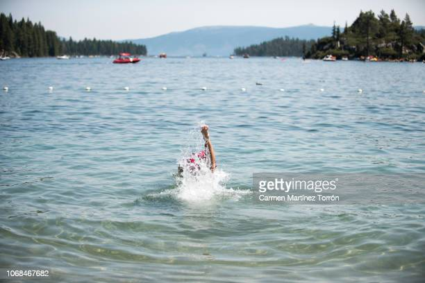 man diving into water in south lake tahoe, california. - carmen bella foto e immagini stock