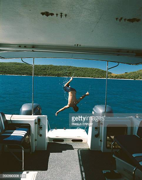 Man diving off back of boat, rear view