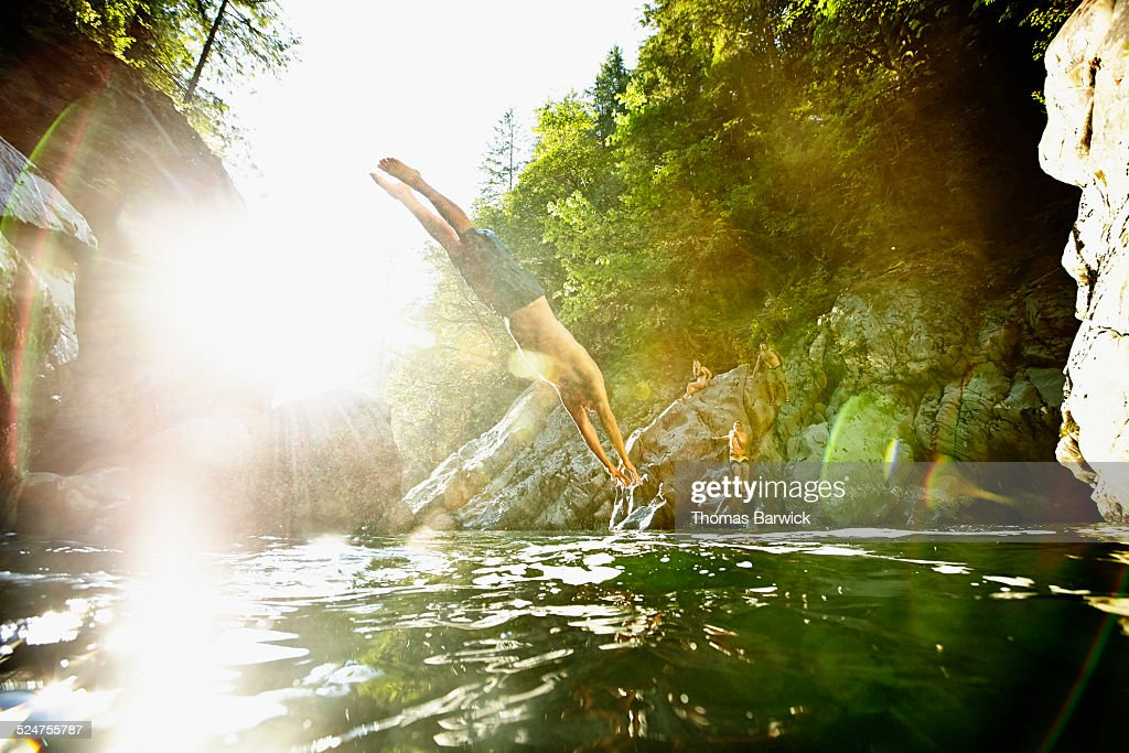 Man diving off boulder into river swimming hole : Stock Photo