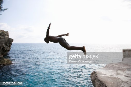 Man Diving Off Cliff Into Sea Sunset Stock Photo