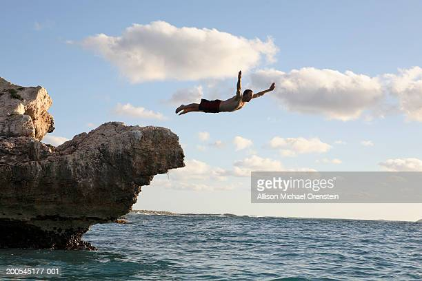 Man diving off cliff into the ocean