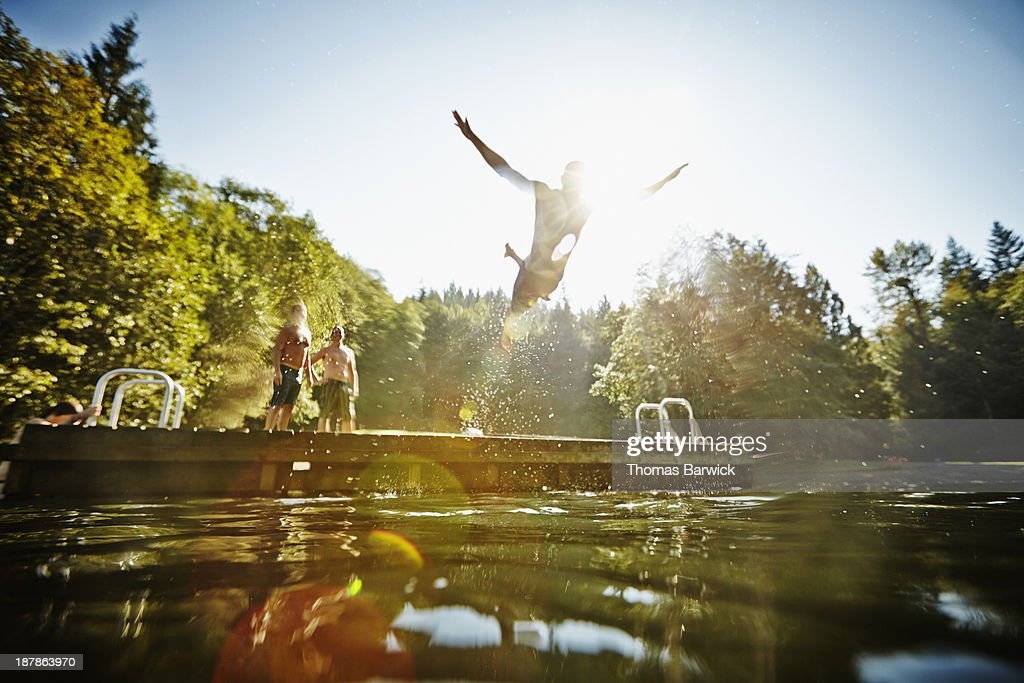 Man diving off dock into lake : Stock Photo