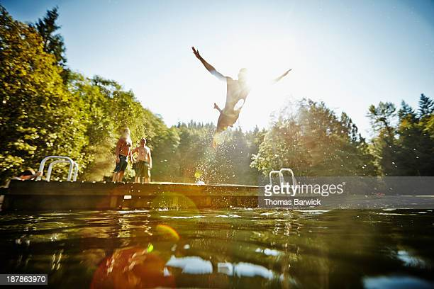 man diving off dock into lake - gegenlicht stock-fotos und bilder