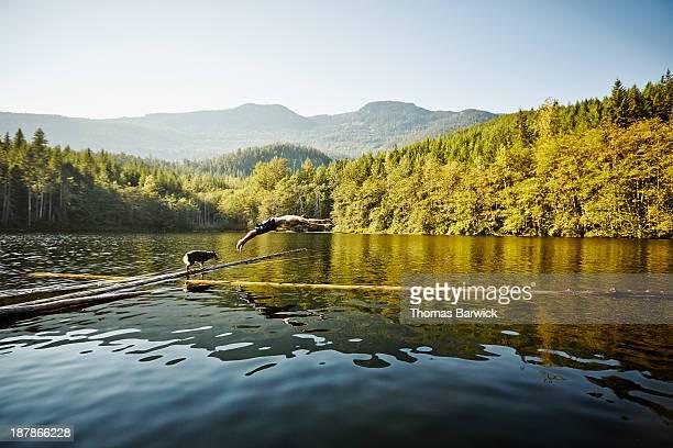 Man diving off log into alpine lake dog watching