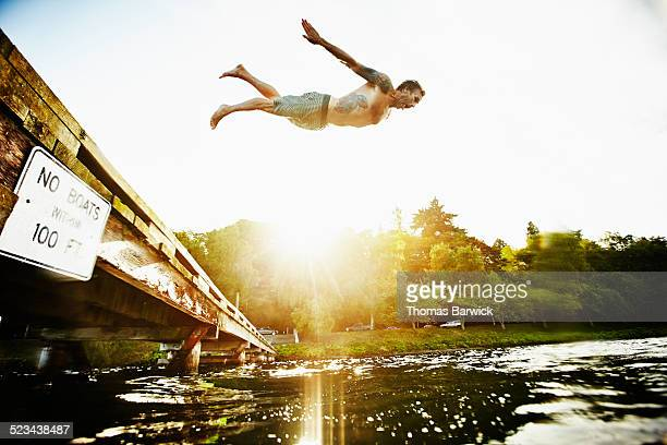Man diving off of dock into lake