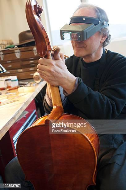 Man doe detail work on cello