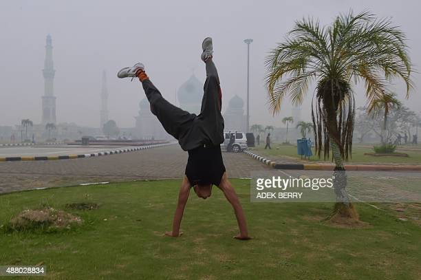 A man does a handstand in the grounds of the AnNur Great Mosque as haze shrouds the Sumatran city of Pekanbaru in Riau province on September 13 2015...