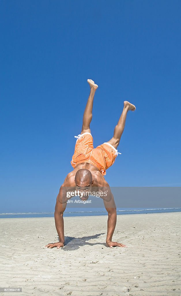 Man does a handstand on beach. : Stock Photo