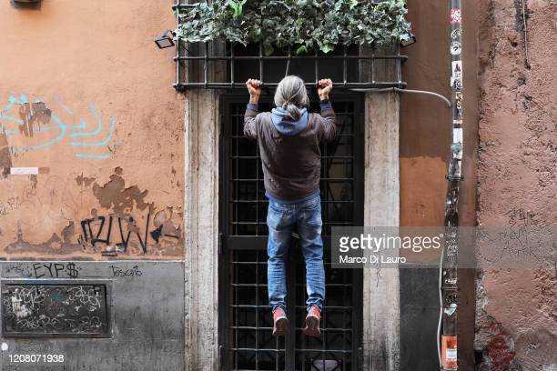 A man does exercises using the door of a apartment on March 22 2020 in Rome Italy As Italy extends its nationwide lockdown to control the spread of...